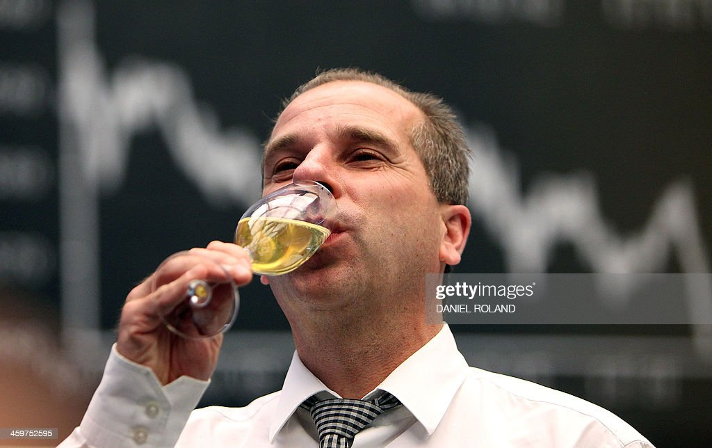 A broker drinks a glass of Champagne near the Dax index graph board at the last trading day of the year at the stock exchange in Frankfurt, western Germany, on December 30, 2013. ROLAND
