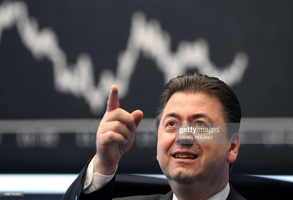 A broker gestures near the Dax index graph board at the last trading day of the year at the stock exchange in Frankfurt, western Germany, on December 30, 2013. ROLAND