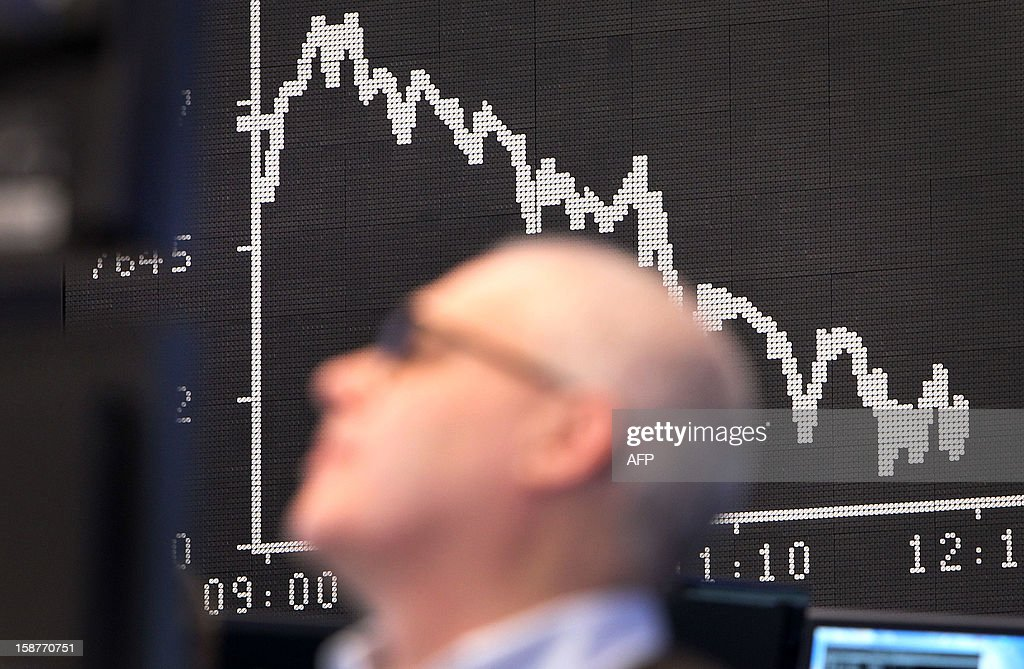 A broker is seen in front of a display showing the German Stock Market Index DAX at the stock exchange in Frankfurt, western Germany, on December 28, 2012, the last day of trade in 2012.