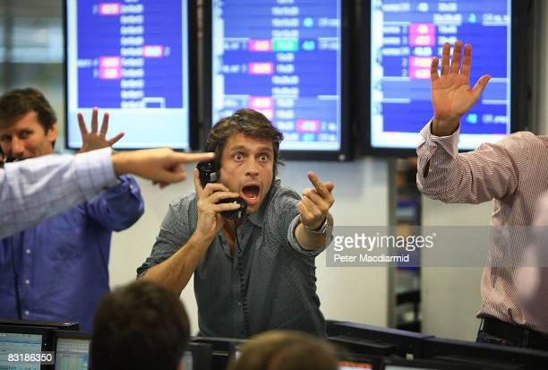 A broker on ICAP's dealing floor calls for prices on October 9 2008 in London Share prices are up on the day as markets react to the interest rate cut