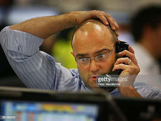 A broker on ICAP's dealing floor looks at prices on his screens on October 9 2008 in London Share prices are up on the day as markets react to the...
