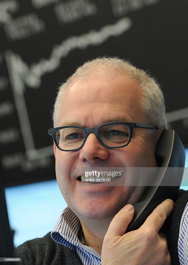 A broker smiles at the Stock Exchange in Frankfurt am Main, on January 2, 2013. Financial markets worldwide eased after the United States averted the so-called fiscal cliff. The German Stock Index (Dax) rose by about two per cent on the first trading day 2013.