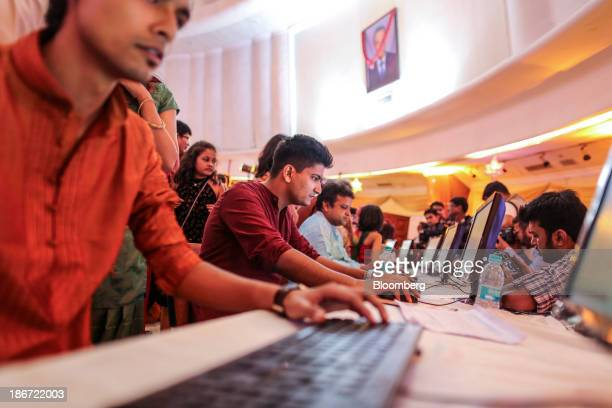 Brokers along with their families trade as ceremonial purchases of stocks are made during the session marking Diwali at the Bombay Stock Exchange in...