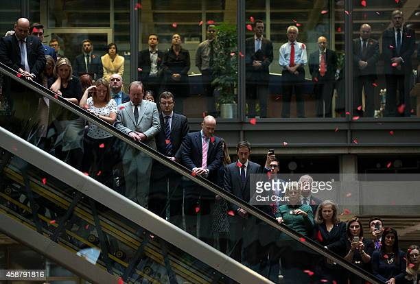 Brokers and underwriters look on as poppies fall during a twominute silence at a Remembrance Day service at the Lloyd's of London building on...