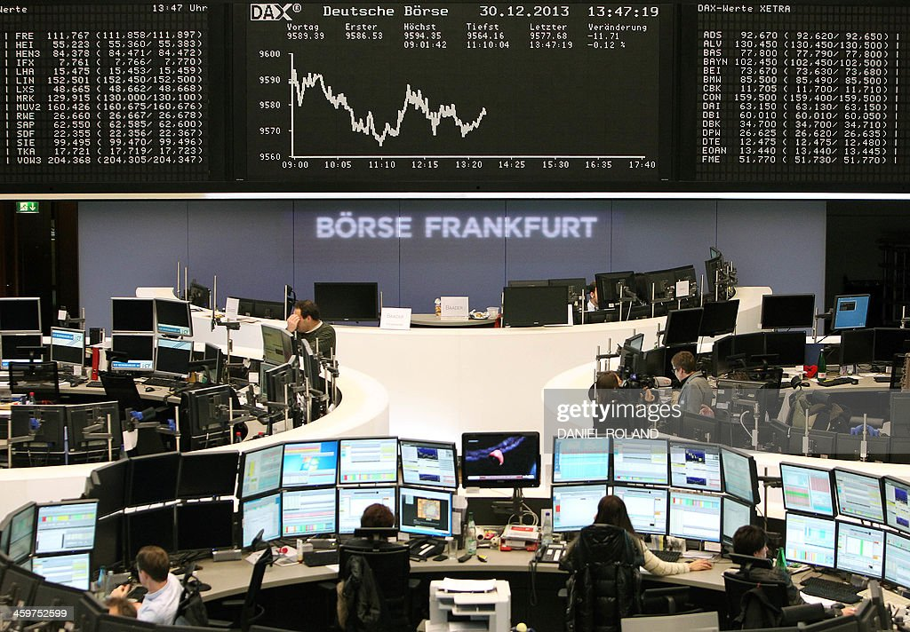 Brokers are pictured near the Dax index graph board at the last trading day of the year at the stock exchange in Frankfurt, western Germany, on December 30, 2013. ROLAND