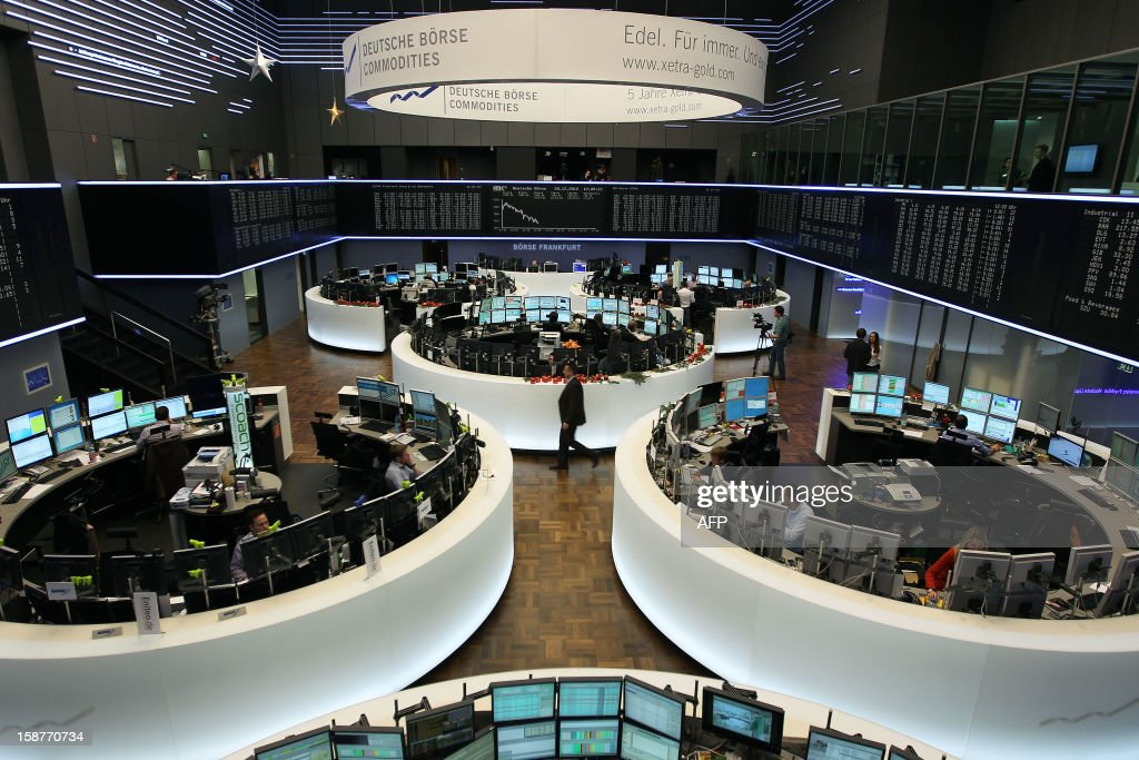 Brokers are seen in front of a display showing the German Stock Market Index DAX at the stock exchange in Frankfurt, western Germany, on December 28, 2012, the last day of trade in 2012. AFP PHOTO / DANIEL ROLAND