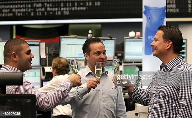 Brokers clink glasses at the German Stock Exchange in Frankfurt am Main western Germany on the last day of trade on December 30 2014 AFP PHOTO /...