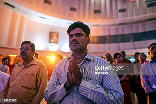 A brokers prays before ceremonial purchases of stocks are made during the session marking Diwali at the Bombay Stock Exchange in Mumbai India on...