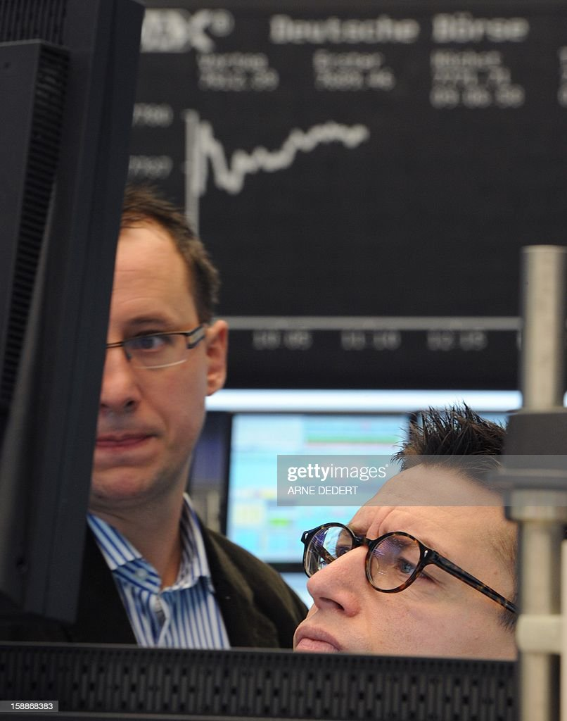 Brokers view their monitor at the Stock Exchange in Frankfurt am Main, on January 2, 2013. Financial markets worldwide eased after the United States averted the so-called fiscal cliff. The German Stock Index (Dax) rose by about two per cent on the first trading day 2013.