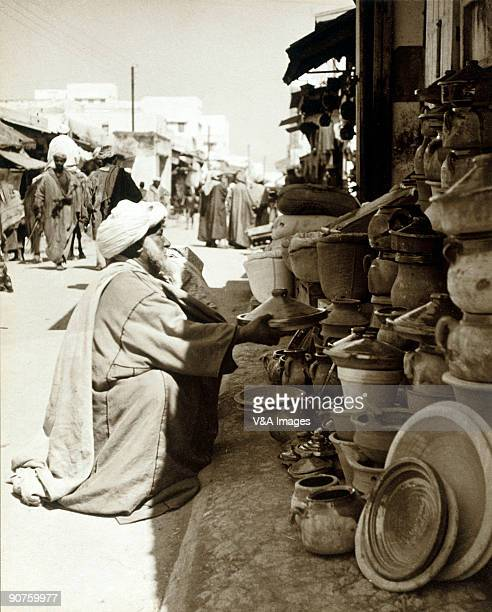 Bromide print Photograph by Ernest R Ashton of a man holding a tagine dish at a pottery stall