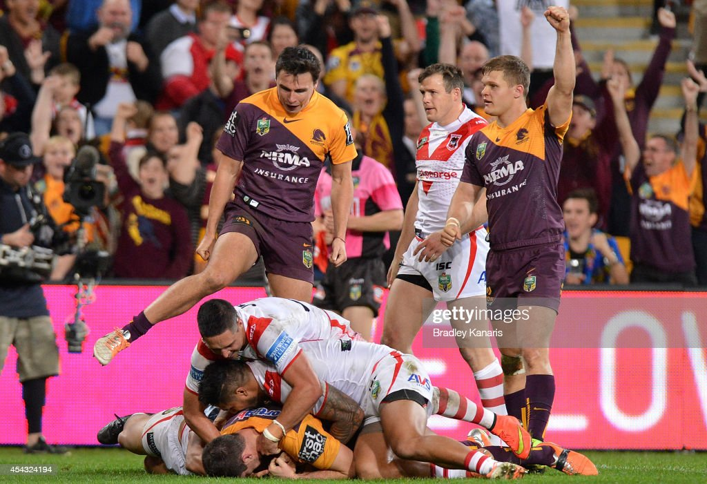 Broncos players celebrate as team mate Matt Gillett of the Broncos scores a try during the round 25 NRL match between the Brisbane Broncos and the St...