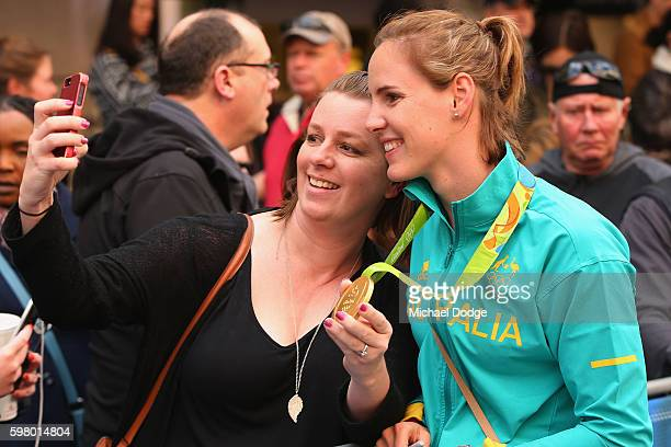 Bronte Campbell lets a fan hold her gold medal during the Australian Olympic Team Melbourne Welcome Home Celebration at Bourke Street on August 31...