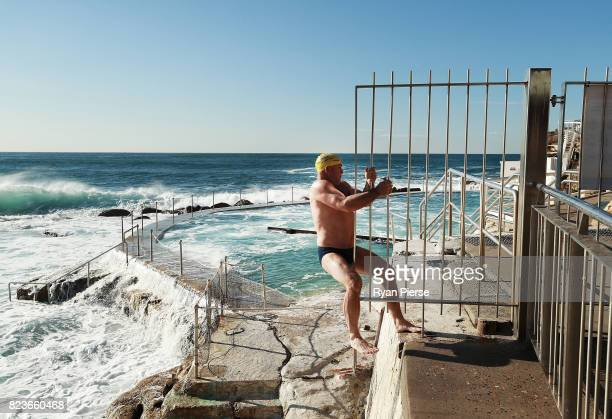 Bronte Splashers Swimming Club member jump around the fence after the pool was closed due to a heavy swell at Bronte Pool on July 23 2017 in Sydney...