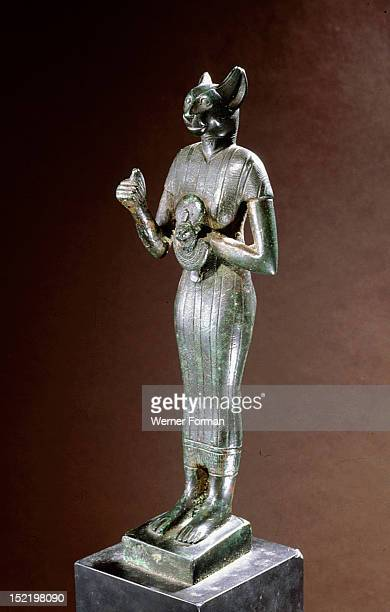 Bronze figure of the cat goddess Bastet standing with raised right arm holding a leonine headed aegis Local deity of the town of Bubastis Bastet was...