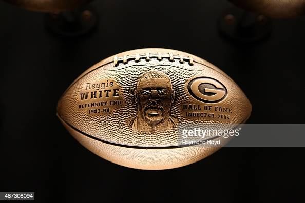 A bronze football honoring Reggie White is on display inside the Green Bay Packers 'Hall Of Fame' inductees room inside the Lambeau Field atrium on...