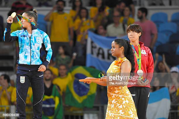 Bronze medalist Ami Kondo of Japan watches gold medalist Paula Pareto of Argentina on the podium at the medal ceremony for the women's 48kg on Day 1...