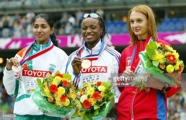 Bronze medalist Anju Bobby George of India gold medalist Eunice Barber of France and silver medalist Tatyana Kotova of Russia during the medal...