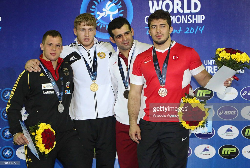 Bronze medalist Cenk Ildem mens GrecoRoman Style 98 kg division pose during the medal ceremony for the men's freestyle wrestling at the Wrestling...