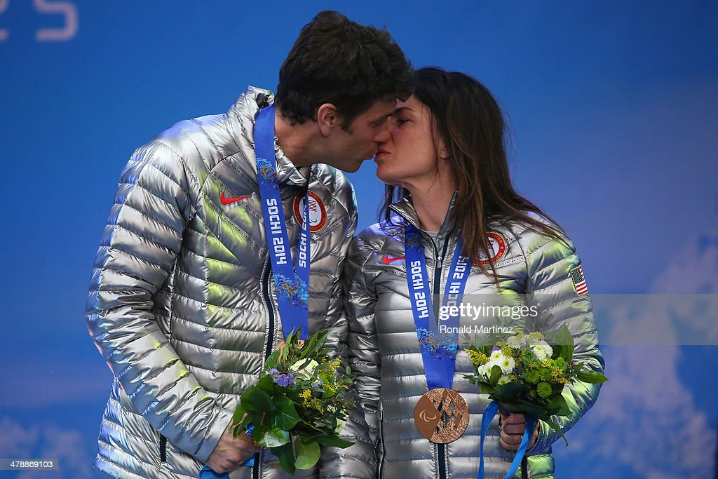 Bronze medalist Danelle Umstead and guide Robert Umstead kiss as they celebrate at the medal ceremony for women's Super Combined Visually Impaired on day eight of the Sochi 2014 Paralympic Winter Games at Laura Cross-country Ski & Biathlon Center on March 15, 2014 in Sochi, Russia.
