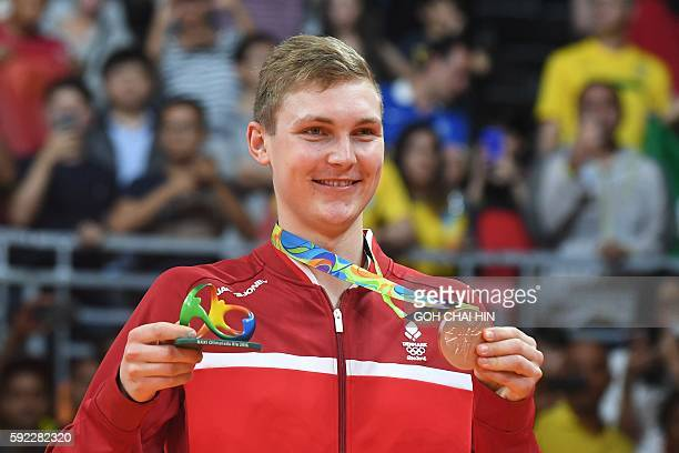 Bronze medalist Denmark's Viktor Axelsen reacts as he stands with his medal following the men's singles Gold Medal badminton match at the Riocentro...