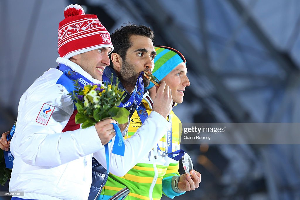Bronze medalist Evgeniy Garanichev of Russia, gold medalist Martin Fourcade of France and Silver medalist <a gi-track='captionPersonalityLinkClicked' href=/galleries/search?phrase=Erik+Lesser&family=editorial&specificpeople=6837118 ng-click='$event.stopPropagation()'>Erik Lesser</a> of Germany celebrate on the podium during the medal ceremony for the Men's Individual 20 km on day 7 of the Sochi 2014 Winter Olympics at Medals Plaza on February 14, 2014 in Sochi, Russia.