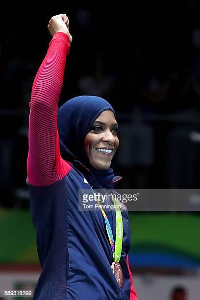 Bronze medalist Ibtihaj Muhammad of the United States celebrates on the podium during the Women's Sabre Team bronze medal match between United States...