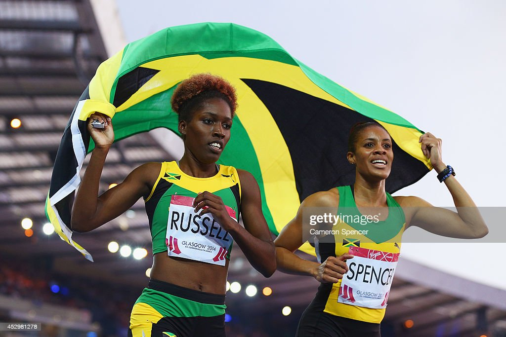 Bronze medalist Janieve Russell of Jamaica and Gold medalist Kaliese Spencer of Jamaica celebrate the Women's 400 metres hurdles final at Hampden...