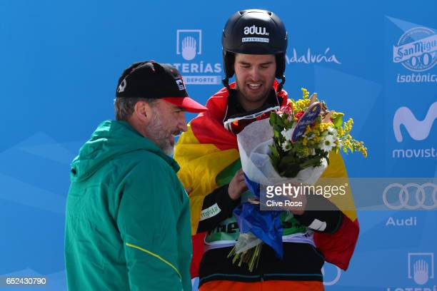 Bronze medalist Lucas Eguibar of Spain is congratulated by King Felipe VI of Spain during the flower ceremony for the Men's Snowboard Cross on day...