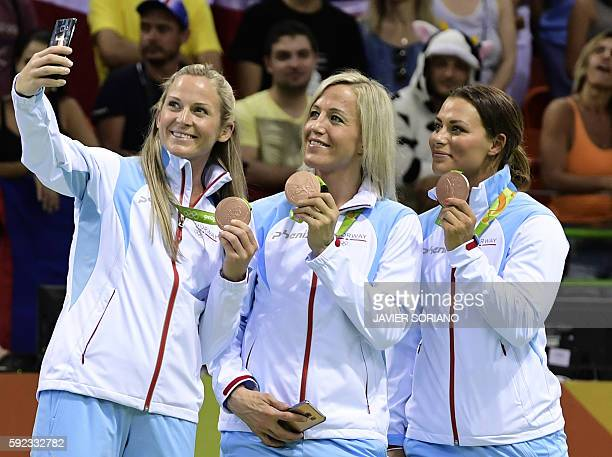 Bronze medalist Norway's left back Ida Alstad takes a selfie of her teammates Norway's pivot Heidi Loke and Norway's right back Nora Mork during the...