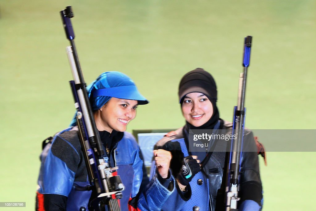 Bronze medalist Nur Suryani Mohamed Taibi (L) and Silver medalist Nur Ayuni Halim (R) pose after the Womens 10m air rifle singles event at the Dr Karni Singh Shooting Range during day seven of the Delhi 2010 Commonwealth Games on October 10, 2010 in Delhi, India.