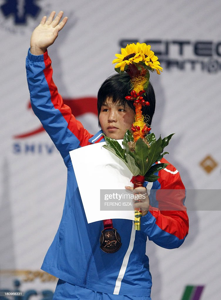 Bronze medalist Peoples Republic of North Korea's Sim Hyang So celebrates on the podium of the women's free style 51 kg category of the World Wrestling Championships in Budapest on September 18, 2013. AFP PHOTO / FERENC ISZA