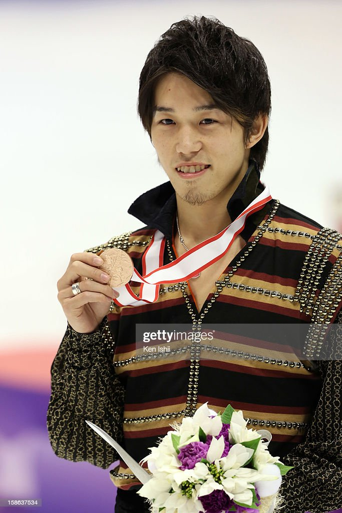 Bronze medalist Takahito Mura poses for photographs at the medal ceremony during day two of the 81st Japan Figure Skating Championships at Makomanai Sekisui Heim Ice Arena on December 22, 2012 in Sapporo, Japan.