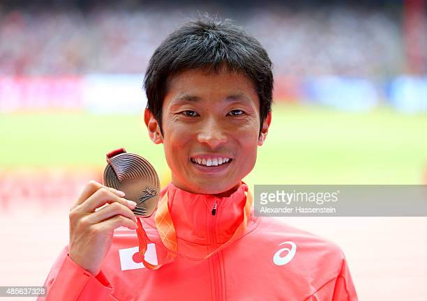 Bronze medalist Takayuki Tanii of Japan poses on the podium during the medal ceremony for the Men's 50km Race Walk final during day eight of the 15th...