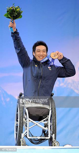 Bronze medalist Takeshi Suzuki of Japan celebrates at the medal ceremony for the Men's Downhill Sitting during day one of Sochi 2014 Paralympic...