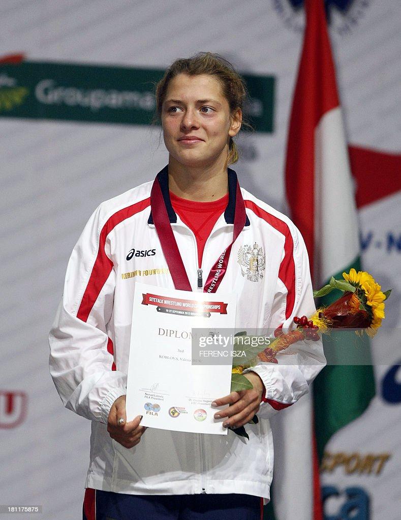 Bronze medalist Ukraina's Iryna Husyak celebrates on the podium of the women's free style 55 kg category of the World Wrestling Championships in Budapest on September 19, 2013.
