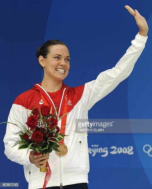 Bronze medalist US swimmer Natalie Coughlin stands on the podium for the women's 100m freestyle swimming final during the medal ceremomy at the...
