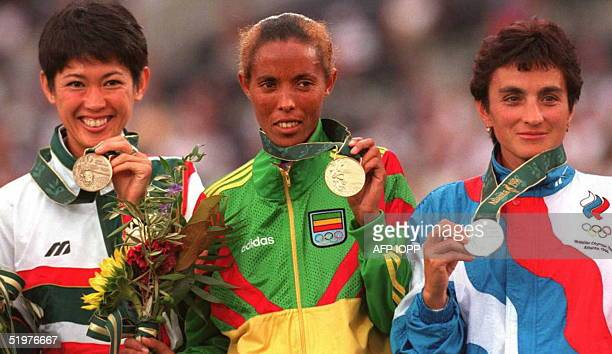 Bronze medalist Yuko Arimori of Japan gold medalist Fatuma Roba from Ethiopia and silver medalist Valetina Yegorova of Russia display their medals...