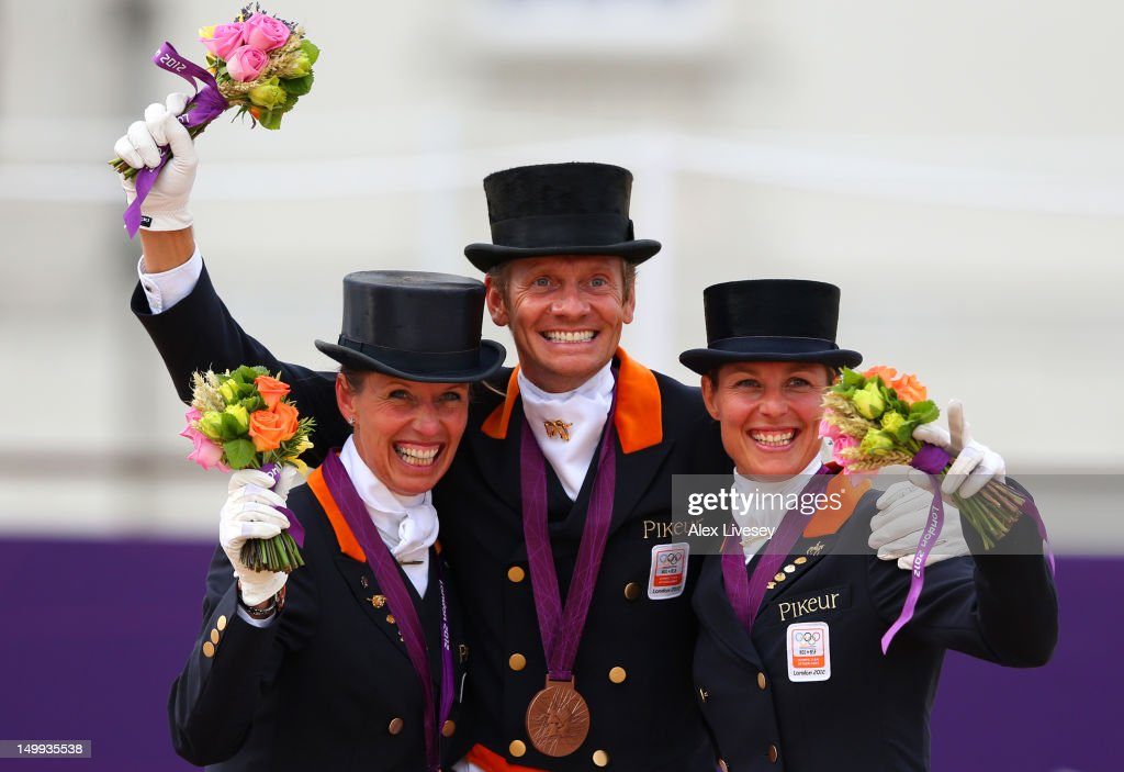 Bronze medalists Anky Van Grunsven, <a gi-track='captionPersonalityLinkClicked' href=/galleries/search?phrase=Edward+Gal&family=editorial&specificpeople=2272233 ng-click='$event.stopPropagation()'>Edward Gal</a> and <a gi-track='captionPersonalityLinkClicked' href=/galleries/search?phrase=Adelinde+Cornelissen&family=editorial&specificpeople=5427385 ng-click='$event.stopPropagation()'>Adelinde Cornelissen</a> of Netherlands celebrate with their medals during the medal cerermony for the Team Dressage on Day 11 of the London 2012 Olympic Games at Greenwich Park on August 7, 2012 in London, England.