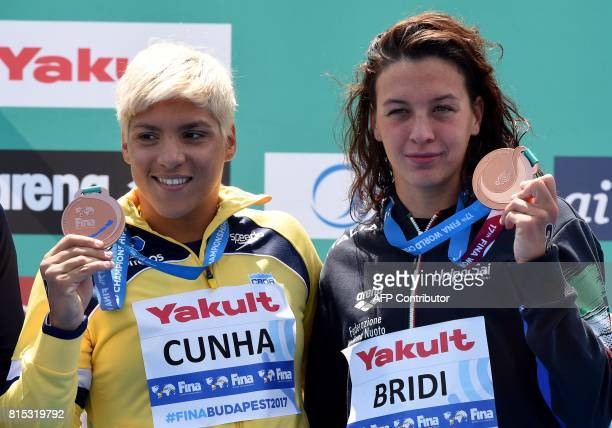 Bronze medalists Brazilian Ana Marcela Cunha and Italian Arianna Bridi celebrate on podium during the medal ceremony after women's 10km open water...