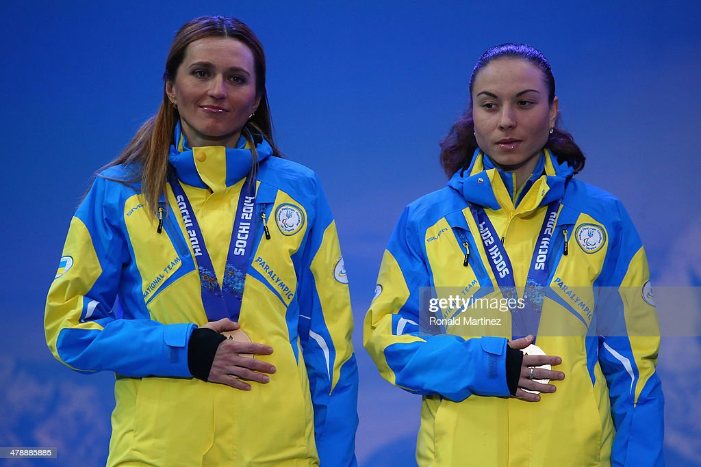 Bronze medalists guide Lada Nesterenko and Oksana Shyshkova of the Ukraine cover their medals at the medal ceremony for the the Women's 12.5km Visually Impaired Biathlon on day eight of the Sochi 2014 Paralympic Winter Games at Laura Cross-country Ski & Biathlon Center on March 15, 2014 in Sochi, Russia.