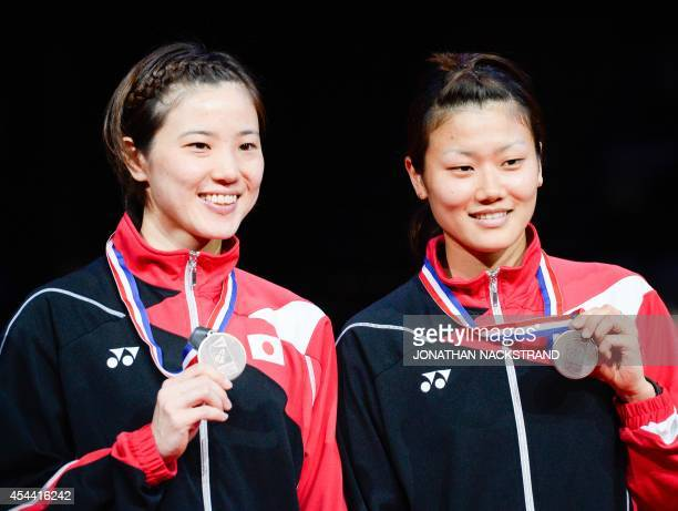 Bronze medalists Japan's Miyuki Maeda and Reika Kakiiwa celebrate on the podium after the women's double final match at the 2014 BWF Badminton World...