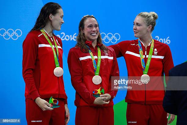 Bronze medalists Kylie Masse Rachel Nicol Penny Oleksiak and Chantal Van Landeghem of Canada celebrate on the podium during the medal ceremony for...