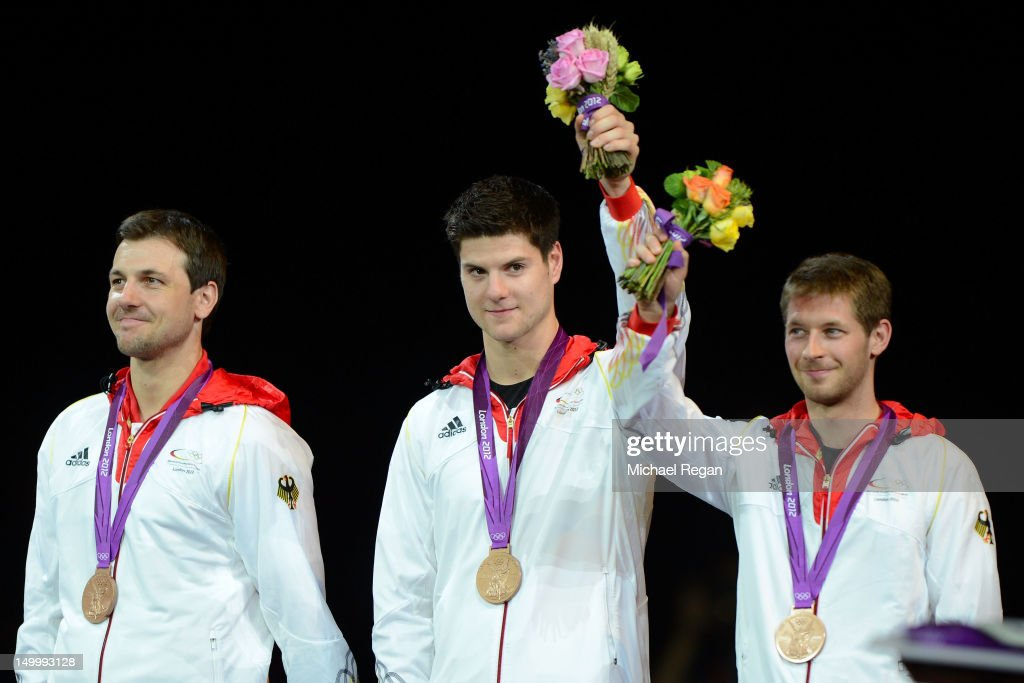 Bronze medalists <a gi-track='captionPersonalityLinkClicked' href=/galleries/search?phrase=Timo+Boll&family=editorial&specificpeople=204430 ng-click='$event.stopPropagation()'>Timo Boll</a>, <a gi-track='captionPersonalityLinkClicked' href=/galleries/search?phrase=Dimitrij+Ovtcharov&family=editorial&specificpeople=4212306 ng-click='$event.stopPropagation()'>Dimitrij Ovtcharov</a> and <a gi-track='captionPersonalityLinkClicked' href=/galleries/search?phrase=Bastian+Steger&family=editorial&specificpeople=655645 ng-click='$event.stopPropagation()'>Bastian Steger</a> of Germany celebrate on the podium during the medal ceremony for the Men's Team Table Tennis gold medal match on Day 12 of the London 2012 Olympic Games at ExCeL on August 8, 2012 in London, England.