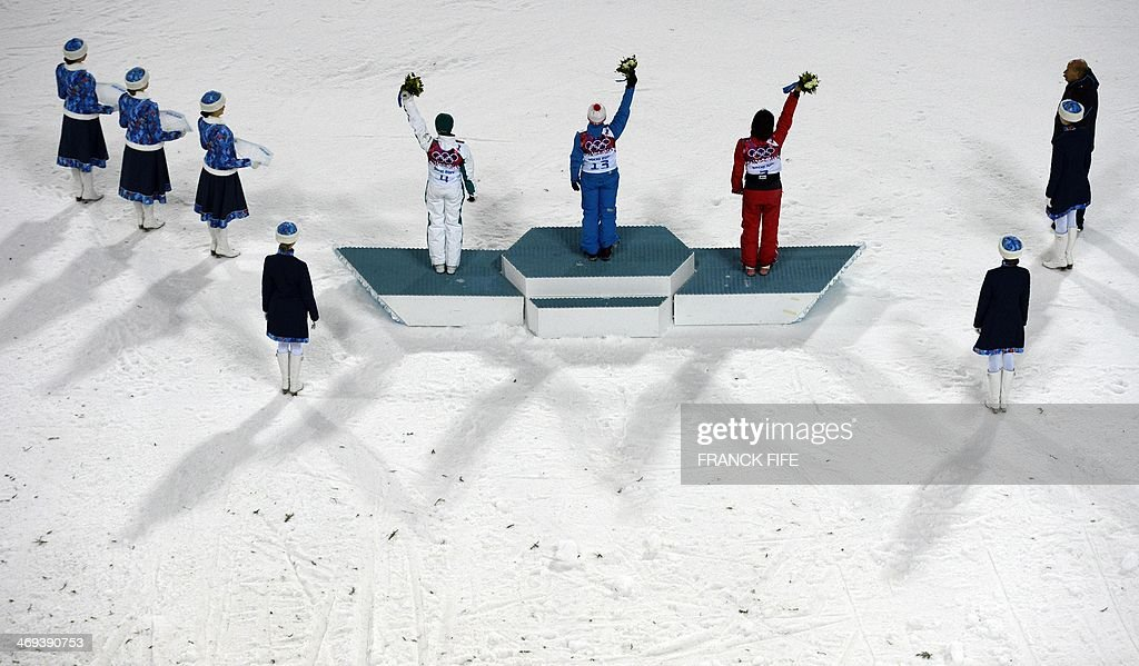 Bronze Medallist, Australia's Lydia Lassila; Gold Medallist, Belarus' Alla Tsuper; and Silver Medallist, China's Xu Mengtao celebrate at the Women's Freestyle Skiing Aerials Flower Ceremony at the Rosa Khutor Extreme Park during the Sochi Winter Olympics on February 14, 2014.