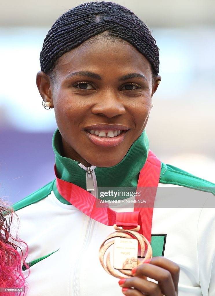Bronze medallist Blessing Okagbare poses on the podium during the medal ceremony for the women's 200 metres at the 2013 IAAF World Championships at the Luzhniki stadium in Moscow on August 17, 2013. AFP PHOTO / ALEXANDER NEMENOV