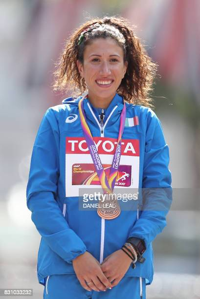 Bronze medallist Italy's Antonella Palmisano poses on the podium during the victory ceremony for the women's 20km race walk athletics event at the...