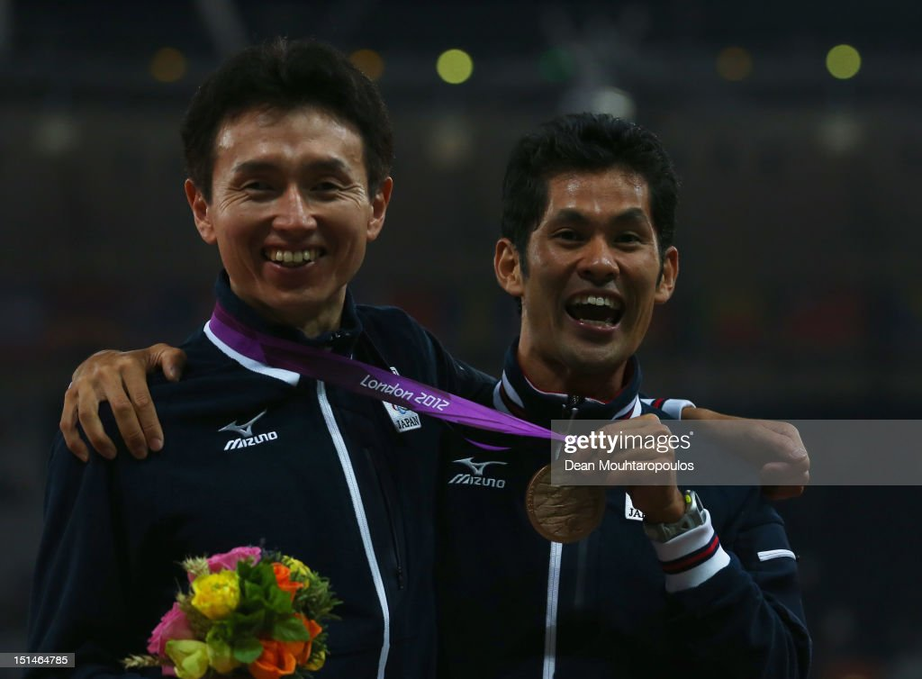 Bronze medallist Shinya Wada of Japan and guide pose on the podium during the medal ceremony for the Men's 5000m T11 Final on day 9 of the London 2012 Paralympic Games at Olympic Stadium on September 7, 2012 in London, England.