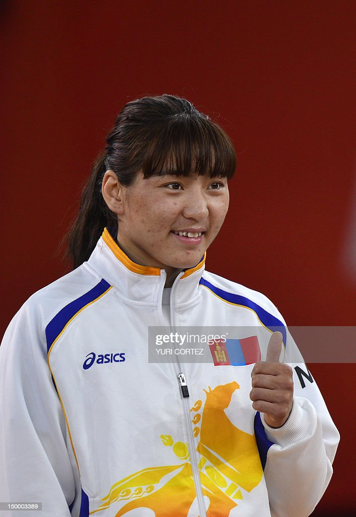 Bronze medallists Mongolia's <a gi-track='captionPersonalityLinkClicked' href=/galleries/search?phrase=Battsetseg+Soronzonbold&family=editorial&specificpeople=7179819 ng-click='$event.stopPropagation()'>Battsetseg Soronzonbold</a> celebrates on the podium of the Women's 63kg Freestyle final match on August 8, 2012 during the wrestling event of the London 2012 Olympic Games.