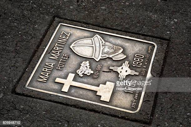 A bronze plaque embedded in the sidewalk in front of the New Mexico Museum of Art in Santa Fe New Mexico honors Native American clay artist Maria...