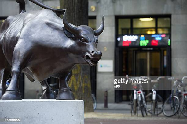 A bronze statue of a bull by ItalianAmerican artist Arturo Di Modica sits on July 5 2012 in front of the Amsterdam stock exchange The artist placed...